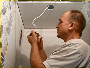 Электрик подключает светильники в туалете
