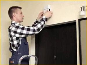 Электрик устанавливает дверной звонок в квартире над дверью