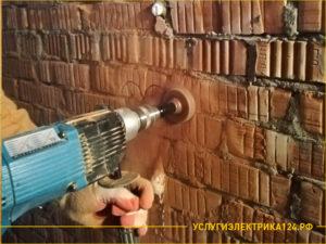 Перфоратор сверлит отверстие под розетки в кирпичной стене
